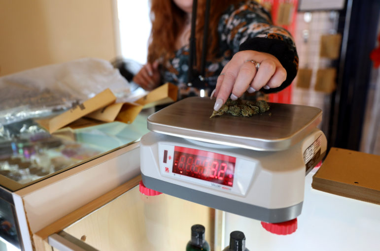 Isis Murphy-Kehoe weighs hemp flower to put in individual packages at her parents CBD and hemp shop, Kickapoo Kind, in Viroqua, Wis., on April 19, 2019. Owner Tim Murphy, who also is a hemp farmer, runs the shop with his wife, Noelle Kehoe. They established Kickapoo Kind in 2018 and moved to a new larger location on Main Street in April 2019. Photo by Emily Hamer / Wisconsin Watch.