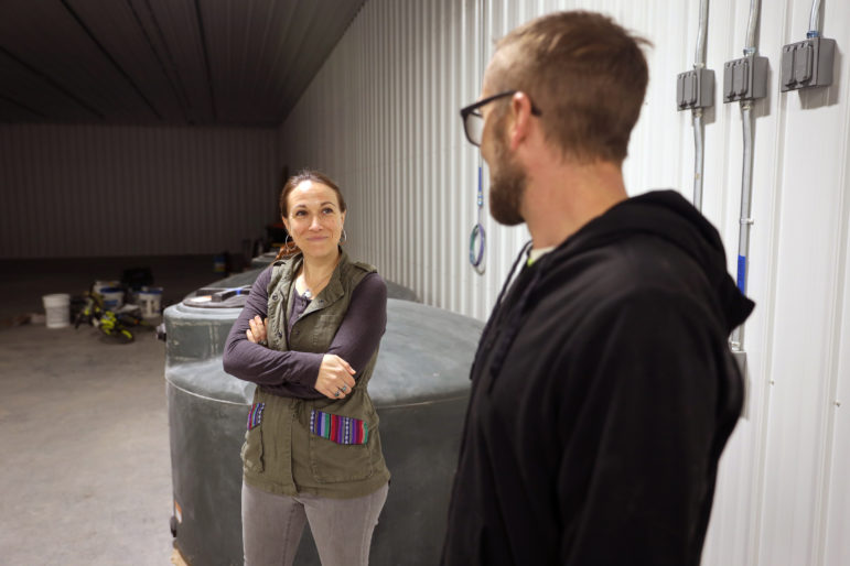 Abbie Testaberg smiles at her husband Jody on April 18, 2019, in what will become one of their hemp grow rooms in River Falls, Wis. Right now, the room serves as a space for their two sons to ride bikes. Testaberg says she hopes if Wisconsin legalizes marijuana, it would ensure that large companies do not dominate the market. Photo by Emily Hamer / Wisconsin Watch.