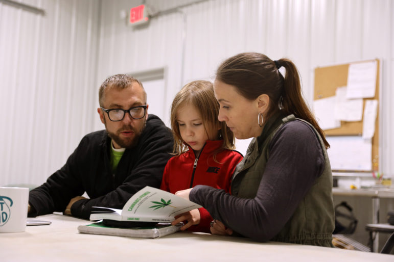 "Abbie Testaberg shows her son Ari, 6, the book she co-wrote called ""Cannabis Primer,"" as her husband Jody looks on, on April 18, 2019. Abbie and Jody Testaberg own a hemp farm, Kinni Hemp Co., in River Falls, Wis. The Testabergs are among hundreds of Wisconsin entrepreneurs who have taken advantage of the recent legalization of hemp, which comes from the same family of plants as cannabis. Photo by Emily Hamer / Wisconsin Watch."