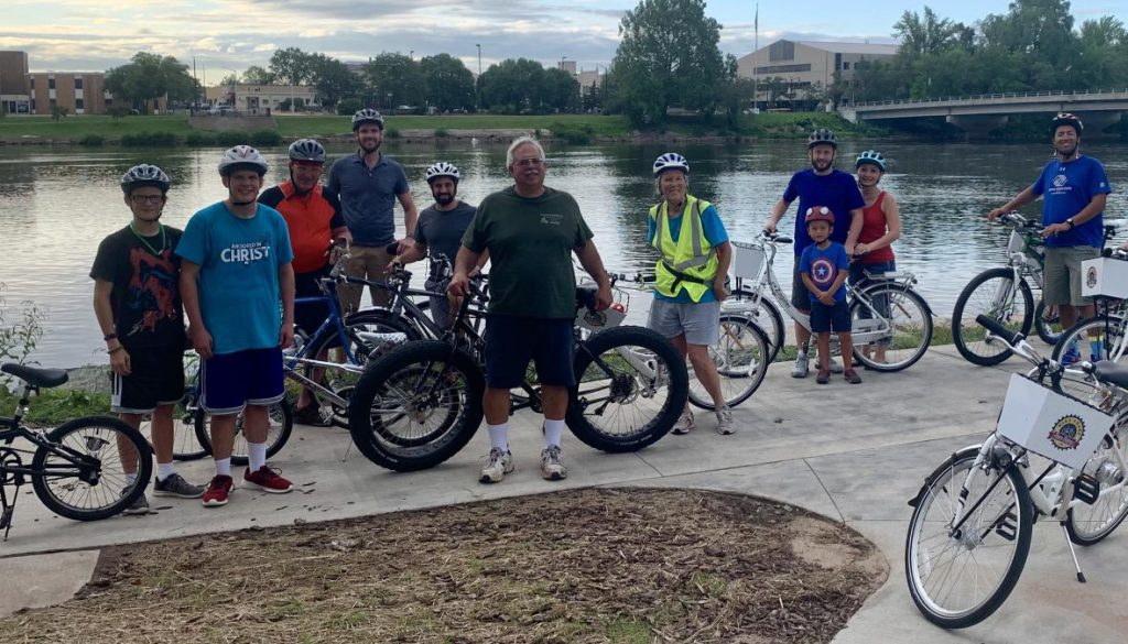 A group of riders at a community bike ride event in Wisconsin Rapids pose for a photo on the city's riverfront. Photo from the Wood County Health Department.