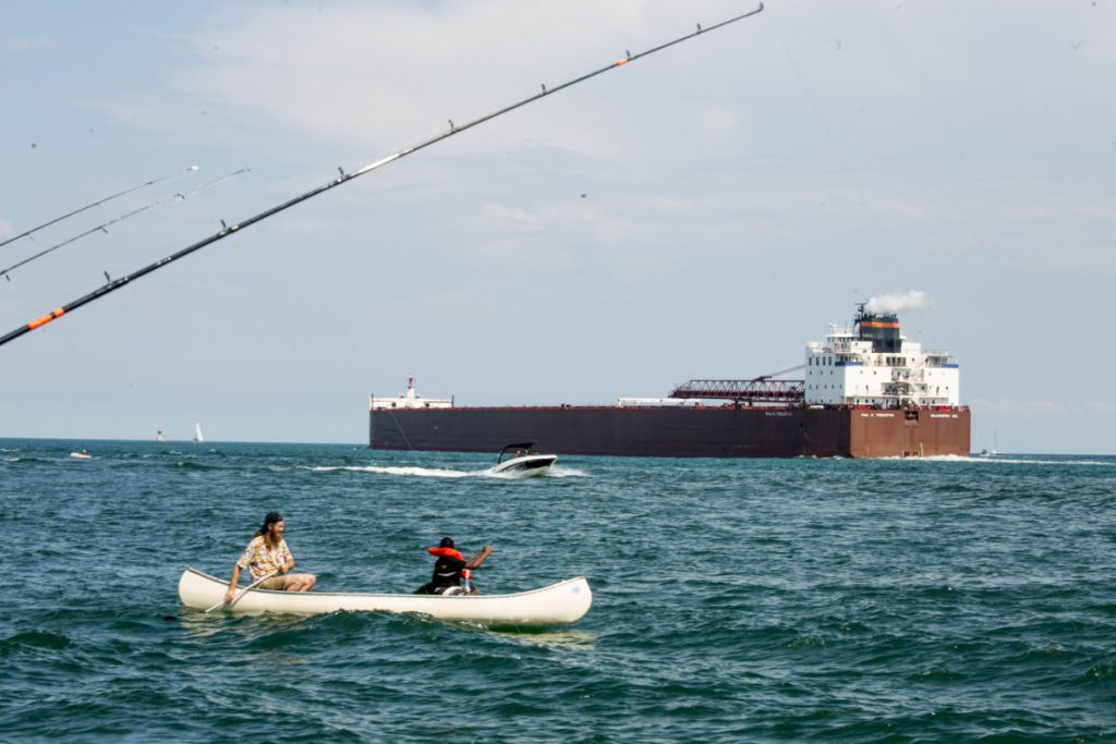 "A canoe, speed boat and fishing lines share the Detroit River with the Paul Tregurtha, a Great Lakes freighter known as a ""laker"", on Aug. 4, 2019. Environmentalists want the U.S. Environmental Protection Agency to require ""lakers"" — freighters that do not leave the Great Lakes — to face ballast restrictions aimed at reducing the spread of invasive species. Photo by Anthony Lanzilote / Bridge Magazine."