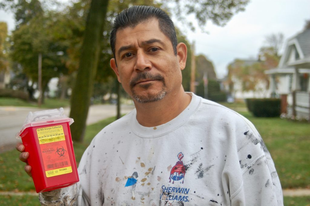 Rafael Mercado, founder of Team HAVOC, holds a container of needles collected during a cleanup on the South Side. (File photo by Edgar Mendez)