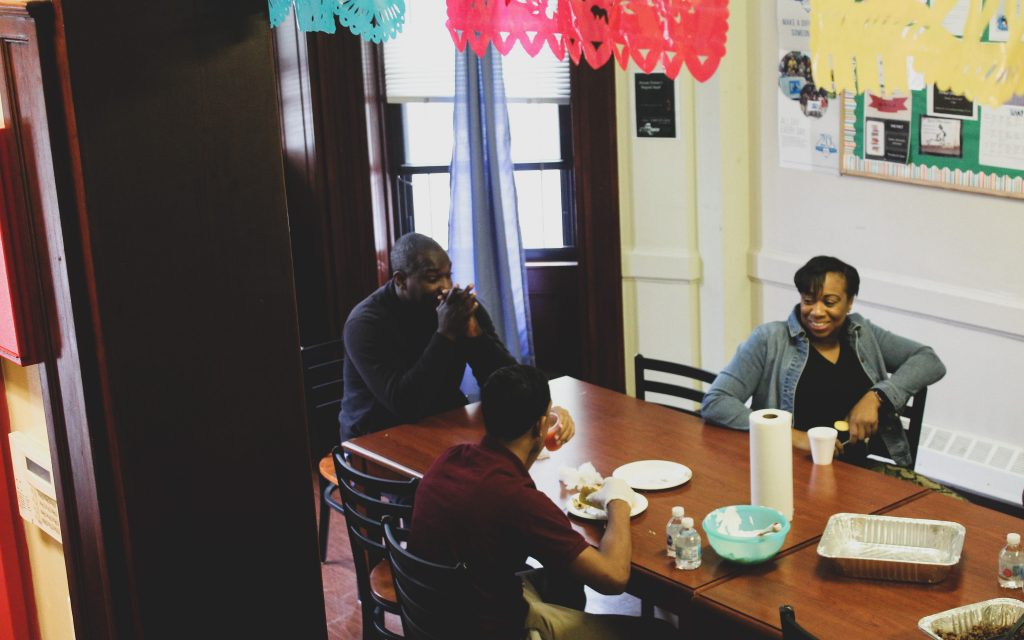 Youths eat lunch with staff members at a big family-style kitchen table at a limited-secure Close to Home facility in Brooklyn, New York. Photo by Allison Dikanovic/NNS.