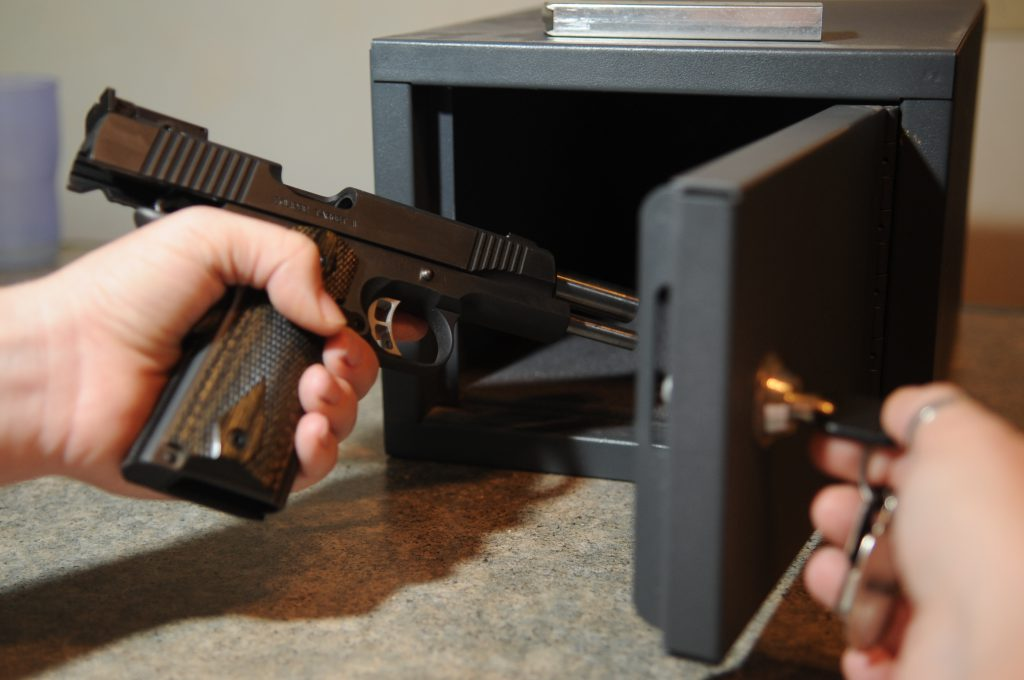 Gun being placed in a safe. Photo by U.S. Air Force Photo/Tech. Sgt. Thomas Dow.