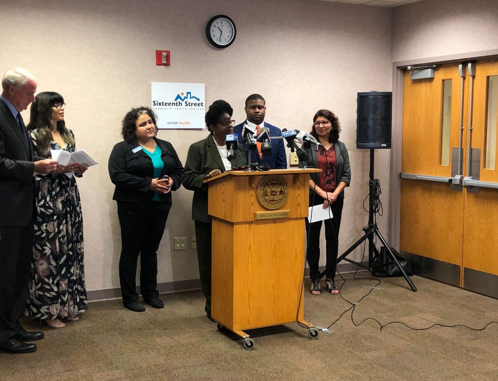 Congresswoman Gwen Moore speaks in front of Mayor Tom Barrett, Commissioner Jeanette Kowalik, Rep. JoCasta Zamarippi, Rep. Kalan Haywood at SSCHS vice president Rosamaria Martinez. Photo by Jeramey Jannene.