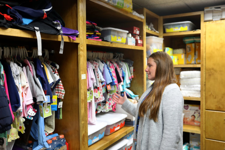 Kari Kerber points to donated clothes and other items in a closet at the Chippewa County Human Services in Chippewa Falls, Wis., that will be distributed to drug-endangered children. The county has been hit hard by an increase in methamphetamine use. In 2018, Child Protective Services put more than 100 children in out-of-home placement due to problems related to meth. Photo taken Sept. 26, 2019.Photo by Parker Schorr/The Cap Times.