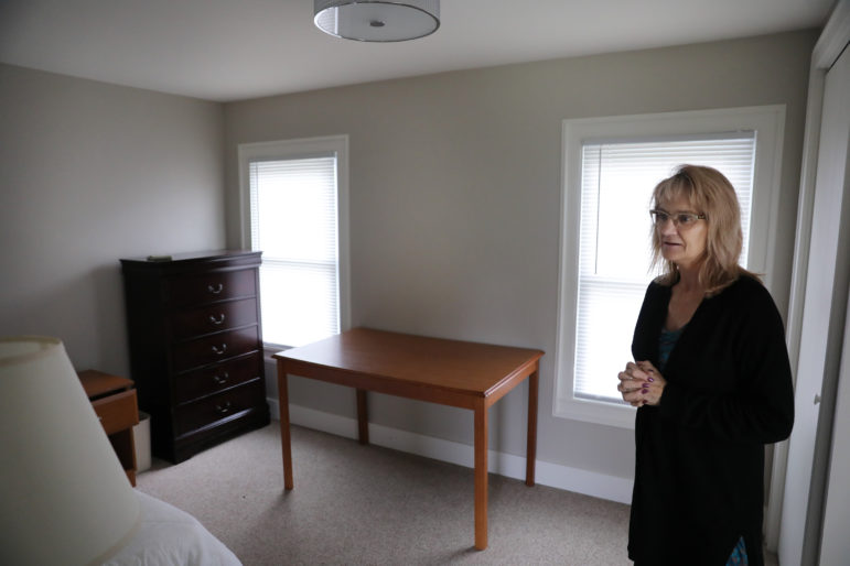 "Kimberly Hill stands in a room of the sole sober-living recovery house in Iowa County, Wis., on Oct. 3, 2019. She manages the facility, which currently houses three women recovering from addictions to opioids. It is funded by a grant that targets opioids, but cannot be used to treat addictions to other substances. It has taken a long time for opioid grants to reach the area, she says, but people are now switching from opioids including heroin to methamphetamine. As a result, she has had to turn people away because they do not have a qualifying addiction. Hill would prefer that the funding be ""for addiction — period — not just an addiction to one thing."" Photo by Parker Schorr / The Cap Times."