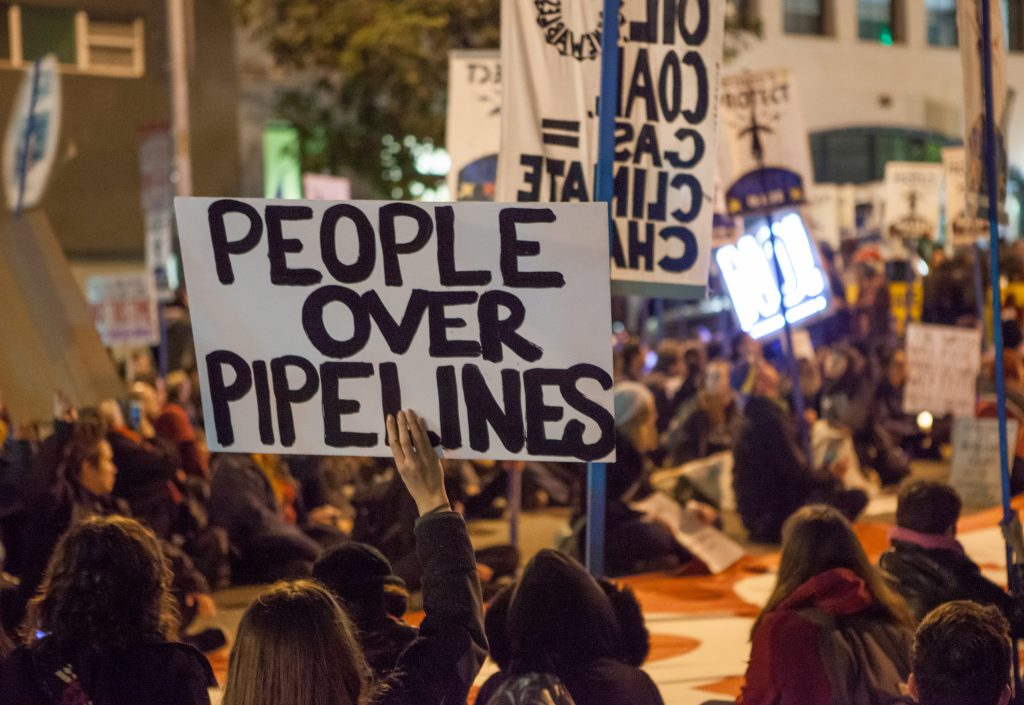 Protesters against the Dakota Access Pipeline and Keystone XL Pipeline hold a sit-in in the street next to the San Francisco Federal Building. Photo by Pax Ahimsa Gethen [CC BY-SA 4.0 (https://creativecommons.org/licenses/by-sa/4.0)].