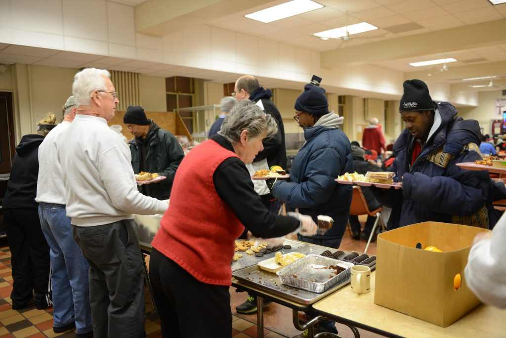 Volunteers serve a meal to guests at St. Benedict the Moor, 924 W. State St., which provides walk-in and 2-1-1 referrals for shelter in extreme cold weather. File photo by Sue Vliet/NNS.