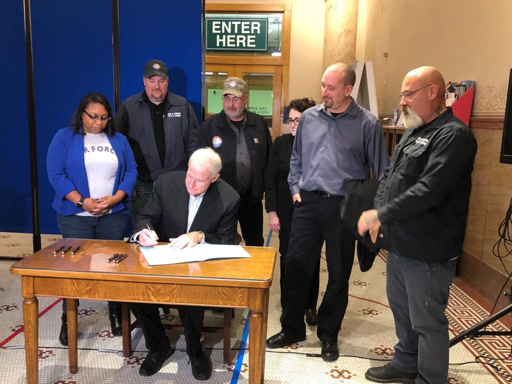 Mayor Tom Barrett signs veterans tiny homes proposal as Alderwoman Chantia Lewis and representatives of Veterans Outreach of Wisconsin look on. Photo by Jeramey Jannene.