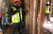 A crew member from Spencer Renovation & Construction demonstrates deconstruction work. Photo by Jeramey Jannene.