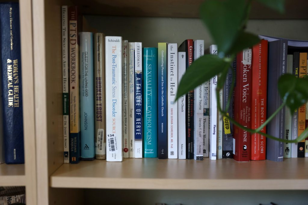 Kathryn Walczyk says she was a victim of sexual abuse by a Norbertine priest when she was a child. She is now a spiritual companion, helping others on their paths to spirituality. Her home office and bookshelf were photographed in Green Bay, Wis. Photo by Coburn Dukehart / Wisconsin Watch.