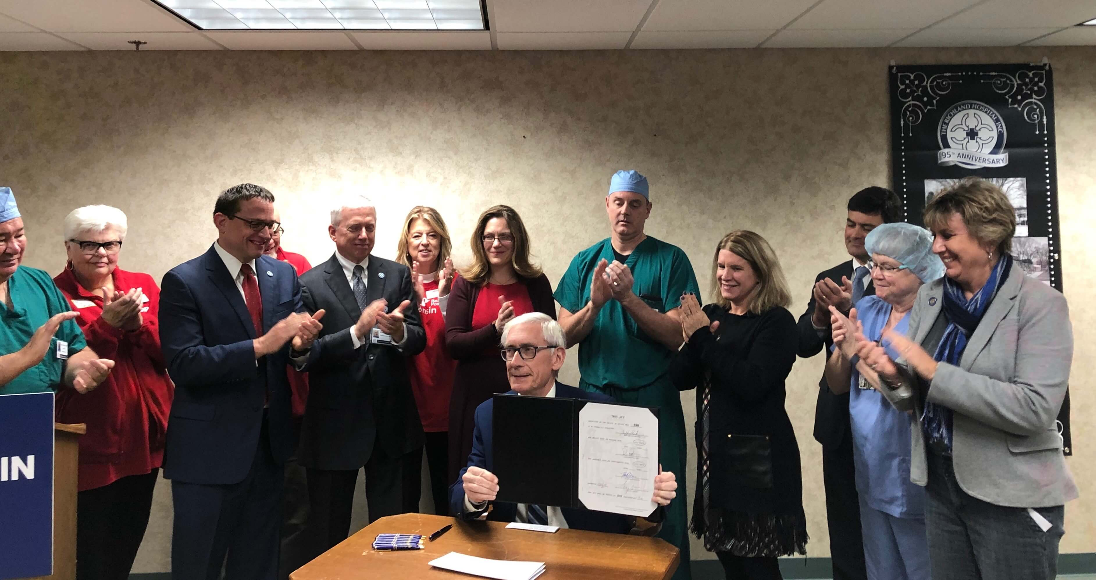 Gov. Tony Evers, seated, after signing Act 56, which expands Medicaid coverage for health care delivered remotely. Photo courtesy of the office of Sen. Jennifer Shilling (D-La Crosse), right. Photo from Shilling's office.