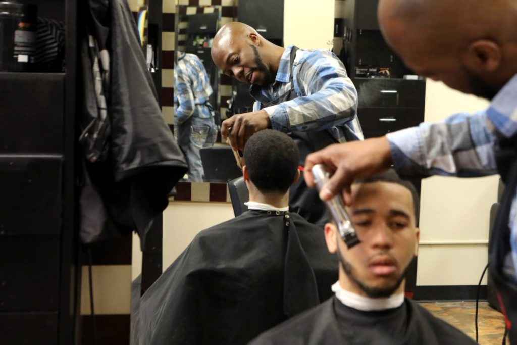 Brian Britt cuts the hair of DeUndre Moore at the Inspire Barber and Beauty Salon, which he owns, in Madison, Wis., on May 8. In addition to owning the Inspire salon, Britt says he is also involved with young adult ministry at Mt. Zion Baptist Church in Madison, and is taking online theology classes. He hopes to create a barber academy for teens at risk of dropping out of school. Photo by Coburn Dukehart / Wisconsin Watch.