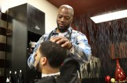 Brian Britt cuts the hair of DeUndre Moore at the Inspire Barber and Beauty Salon, which he owns, in Madison, Wis., on May 8. Britt opened the salon in 2017 and said he had difficulty finding a space to rent due to having a number of convictions on his record, including possession with intent to deliver marijuana in 2000. Photo by Coburn Dukehart/Wisconsin Watch.