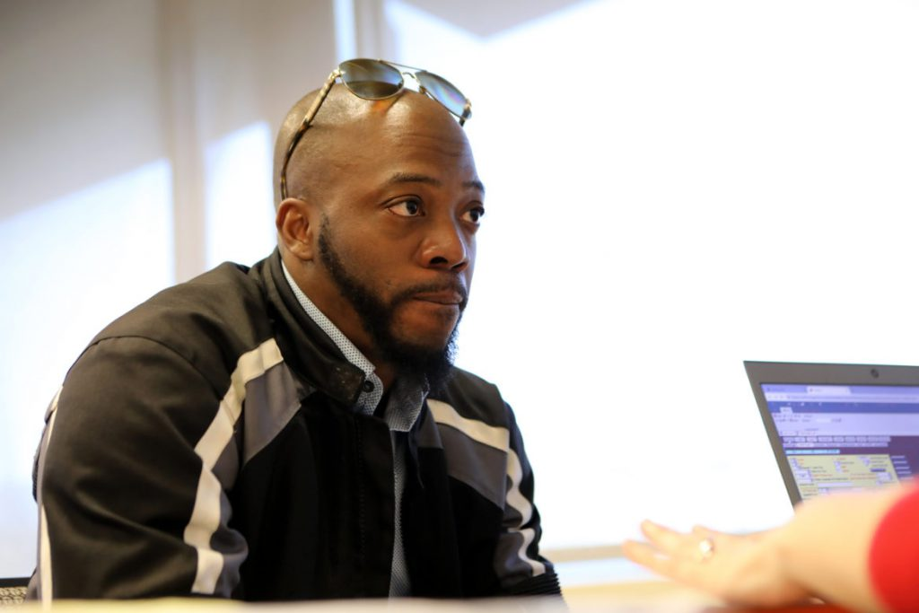Brian Britt of Madison, Wis., meets with attorney Maggie Niebler-Brown during the intake process at an expungement clinic put on by the Urban League of Greater Madison in Madison on May 4. After going through the clinic he learned that under the current law the charges he was hoping to remove from his record cannot be expunged. Britt opened Inspire Barber and Beauty Salon in 2017 but struggled to find a location for the business. His rental applications for commercial spaces were routinely denied, which he believes was the result of his convictions. Photo by Coburn Dukehart / Wisconsin Watch.
