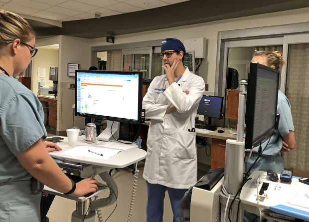 Dr. Marc de Moya, center, chief of trauma and acute care surgery at Milwaukee's Froedtert Hospital, listens to Amy Murphy, left, a fellow of osteopathic medicine at Medical College of Wisconsin, give an update on patients in the surgical intensive care unit. on Aug. 28, 2019. Photo by Corrinne Hess/WPR.