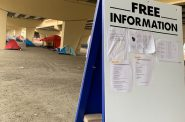 An easel sits under the Marquette Interchange where Milwaukee County and other non-profits post information about services for homeless residents on October 24, 2019 by Alana Watson, WPR.