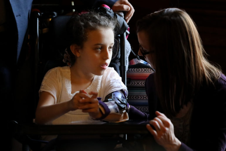 Norah Lowe, from Merrimac, Wis., who suffers from Rett syndrome, a neurological disorder, spoke using a computer after Rep. Melissa Sargent, D-Madison, announced plans to introduce a bill to fully legalize marijuana on April 18, in Madison, Wis. Sargent introduced the bill on May 17. Norah is seen with her mother Megan Lowe. Photo by Coburn Dukehart / Wisconsin Watch.