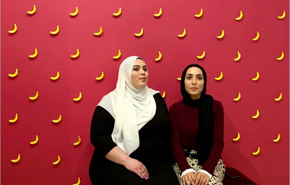 Nayfa Naji (left) and Amal Azzam pose in front of the banana wall during Fanana Banana's second art show in Walker's Point in November. Photo by Claudia Delgadillo/NNS.