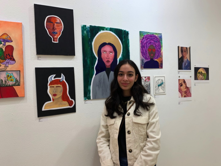 Lena Mahmoud, a 17-year-old Franklin High School student, stands in front of her paintings. Photo by Claudia Delgadillo/NNS.