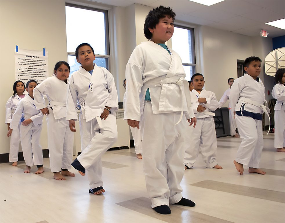 Jake Lee, front, stands with other taekwondo class members as they await commands from their instructors. Photo by Liz Dohms/WPR.