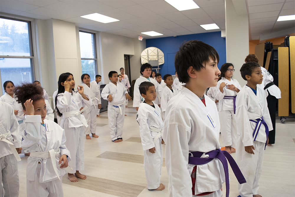 Jonah Lee, foreground, leads a line of white belt students through a series of taekwondo exercises at Seeds of Health Elementary School. Photo by Liz Dohms/WPR.