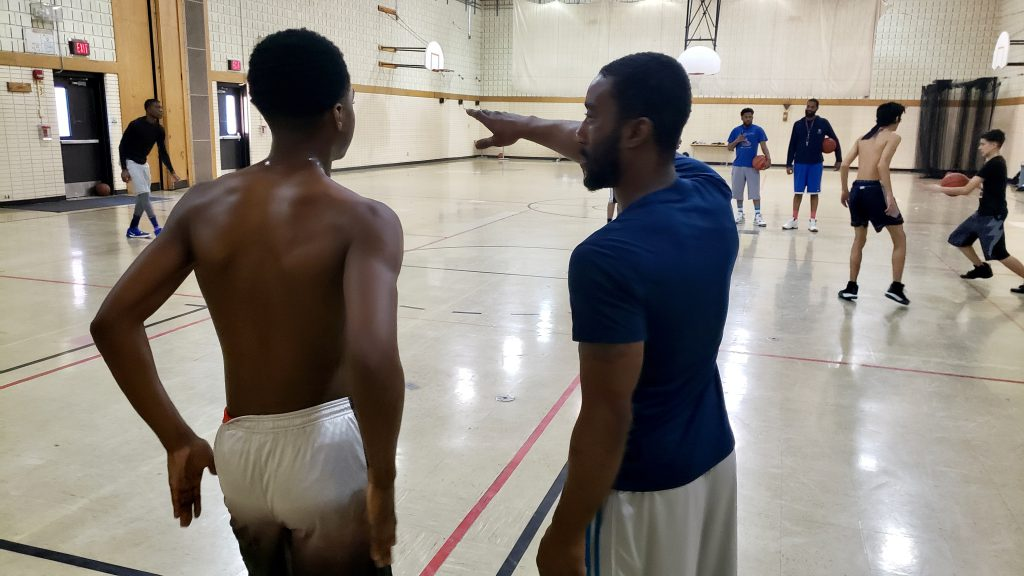 Assistant head coach Mike Causey provides instruction to 17- year-old junior Jamerian Sumler. Photo by Edgar Mendez/NNS.