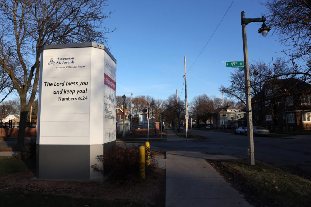 Ascension SE Wisconsin Hospital–St. Joseph Campus in Milwaukee serves a predominantly black, low-income neighborhood, and is located between a busy commercial street on one side, and a neighborhood on the other. A Bible verse is seen on a sign outside the building. Photographed on Dec. 6. Photo by Coburn Dukehart/Wisconsin Watch.