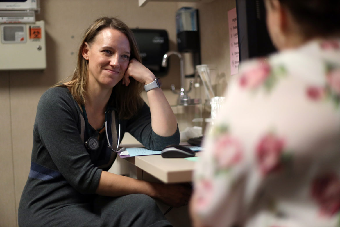 """Dr. Angela Gatzke-Plamann is seen at the Necedah Family Medical Center in Necedah, Wis., on November 7, 2019, doing a check-in with Catina Stoflet, 35, who has been on medication-assisted treatment for seven months. """"There isn't another me just down the road. I'm the only one here,"""" says Dr. Gatzke-Plamann. """"So if I can fulfill that need, then I should do that. And I don't think that's something that urban or suburban physicians have to deal with."""" Photo by Coburn Dukehart/Wisconsin Watch."""