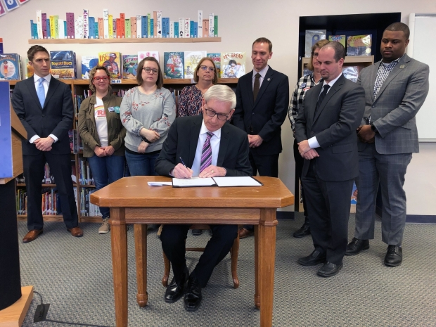 Gov. Tony Evers, center, vetoes the GOP-backed income tax cut Wednesday, Feb. 26, 2020, at Lincoln Elementary School in Wauwatosa, Wis. Photo by Corrinne Hess/WPR.