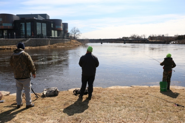 "Eric Barnhardt, of Eau Claire, (right) fishes for walleye with his stepson and grandson along the confluence of the Eau Claire and Chippewa rivers at Phoenix Park near downtown Eau Claire. He said he's been ""cooped up"" since Gov. Tony Evers limited social gatherings of 10 people or more and waiting for the spring spawning run of walleye is a good way to get outside the house. Photo by Rich Kremer/WPR."