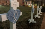 Lutheran Church Charities provided signs for vigil goers to write comforting messages on. The organization will send the signs to the victims families. Photo by Alana Watson/WPR.