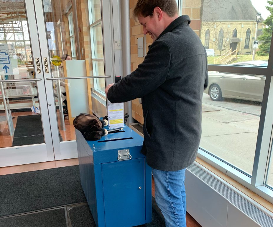 Jeramey Jannene deposits his absentee ballot in a City of Milwaukee drop box. Photo by Alison Peterson.