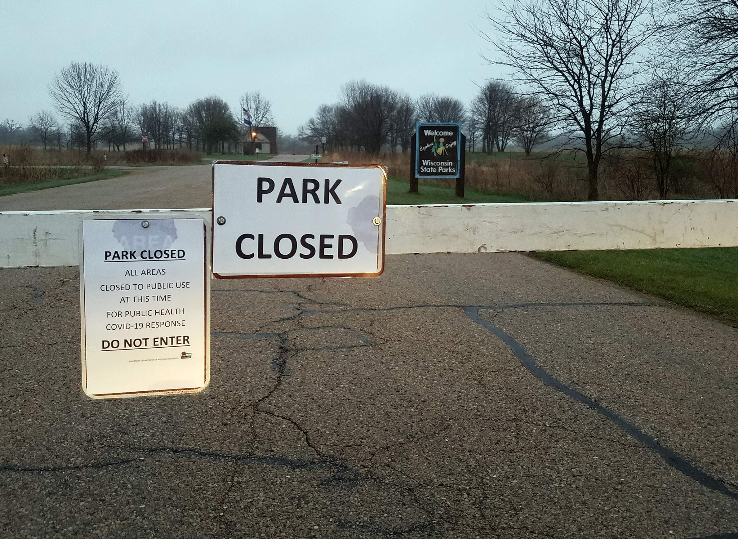 Governor Nelson State Park in Dane County was one of dozens of state parks in Wisconsin ordered closed on April 9, 2020 due to overcrowding and other issues amid the COVID-19 pandemic. Most state parks were ordered to reopen on May 1 with reduced capacity limits, distancing requirements and other changes in place. This photo from April 29 shows a sign at a park entrance noting the closure. Photo by Kristian Knutsen/WisContext.
