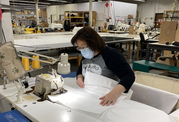 Stormy Kromer employee Penny Linnemanstons sews gowns that are being produced for health care workers and first responders during the coronavirus pandemic. Photo courtesy of Stormy Kromer/WPR.