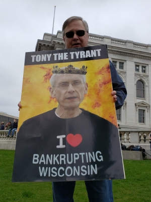 """A protester holds a sign at a rally against Wisconsin's """"Safer at Home"""" order on April 24, 2020 at the Wisconsin State Capitol Building. Shawn Johnson/WPR"""