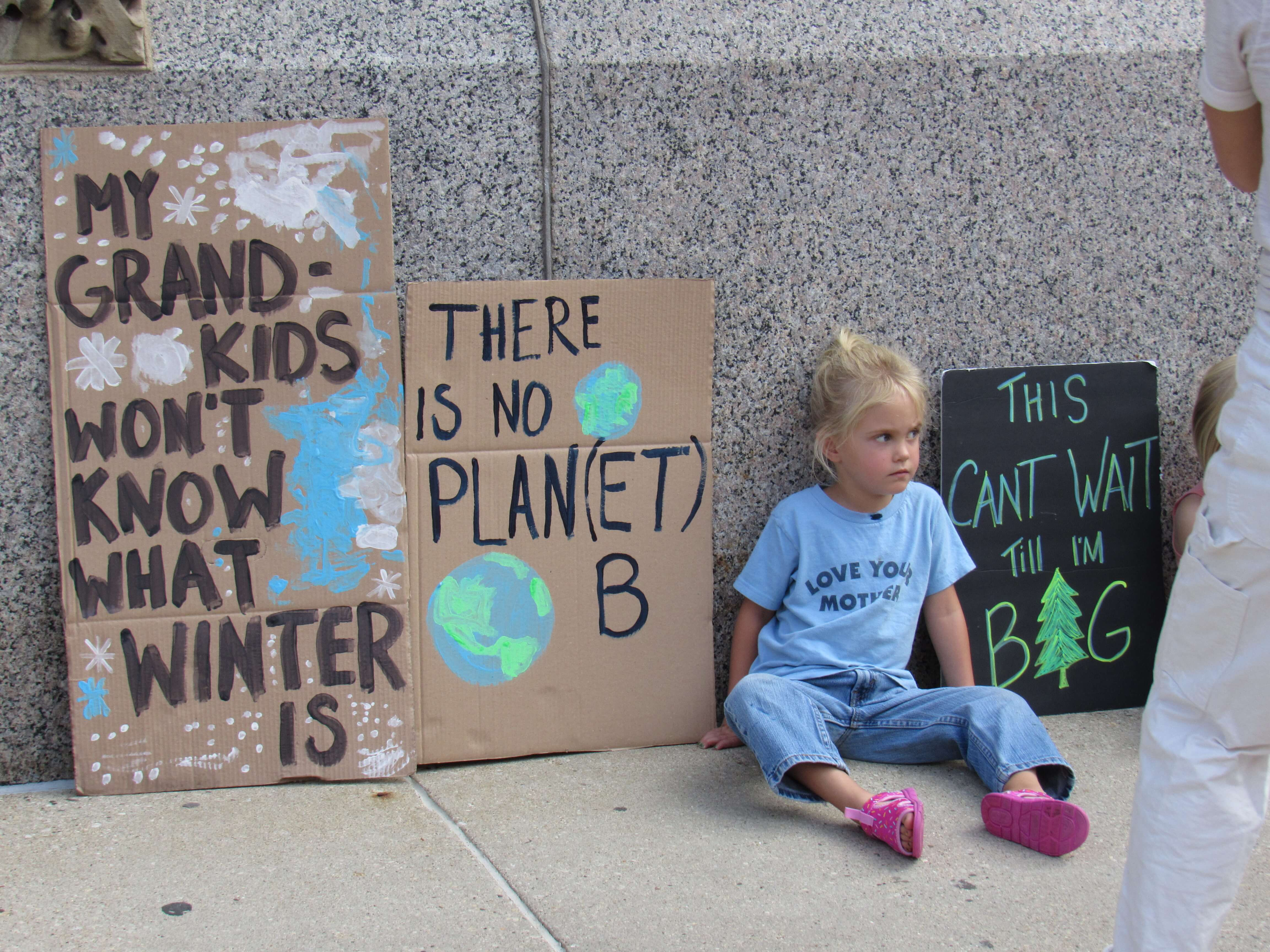 Child sits with signs at Milwaukee climate march 2019. Photo by: Isiah Holmes