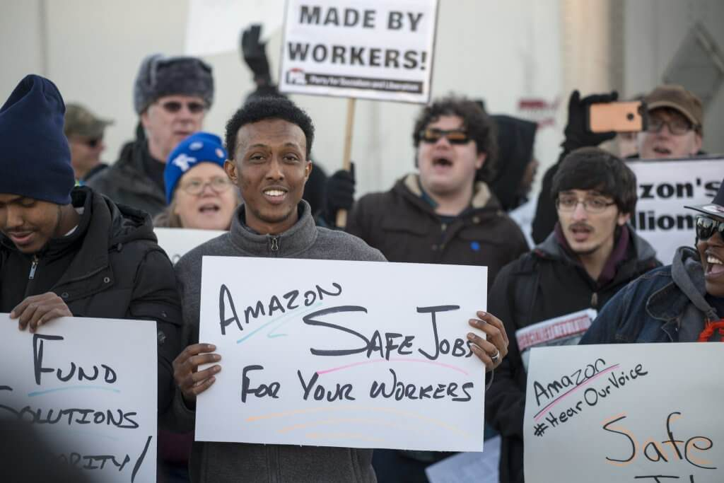 Workers at Amazon protest unsafe working conditions in Shakopee, Minn., in December 2018. The COVID-19 pandemic has increased concerns about job health and safety as employees are being called back to work. Photo by Fibonacci Blue. (CC BY-2.0). https://creativecommons.org/licenses/by/2.0/legalcode