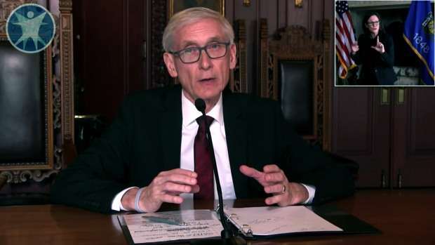 "Gov. Tony Evers says his administration is looking ""very actively"" at relaxing regulations on medical professionals during the COVID-19 crisis. He is seen here answering reporters' questions by video and teleconference on March 24, 2020. Wisconsin Department of Health Services via YouTube."