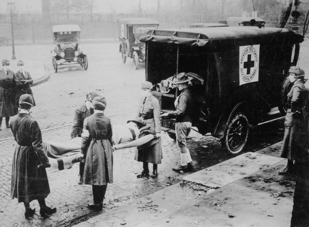 Masked American Red Cross attendants in St. Louis remove the body of a flu victim in 1918, a common scene in cities around the country at the time of the pandemic. Wisconsin was the only state to confront the 1918 flu pandemic with uniform, statewide shutdown measures, which limited deaths, historians say. Photo courtesy of the National Archives/Wisconsin Watch.