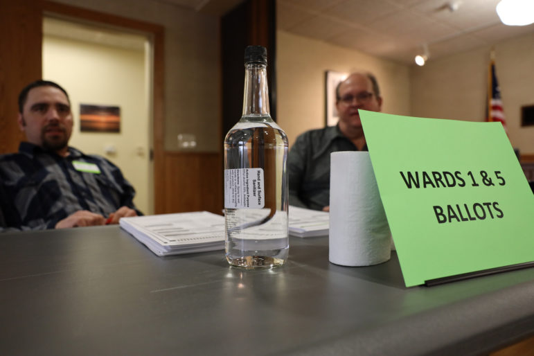 A bottle of hand sanitizer is seen at the polling location at Sevastopol Town Hall in Sevastopol, Wis., during the election on April 7, 2020. Poll workers like Kim Flok, left, and Dennis Schartner, right, were instructed to wipe down surfaces every 10 minutes. Photo by Coburn Dukehart/Wisconsin Watch.