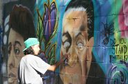 Aisha Valentin paints Supreme Court Justice Thurgood Marshall in a civil rights mural in Harambee. Photo by Jeramey Jannene.