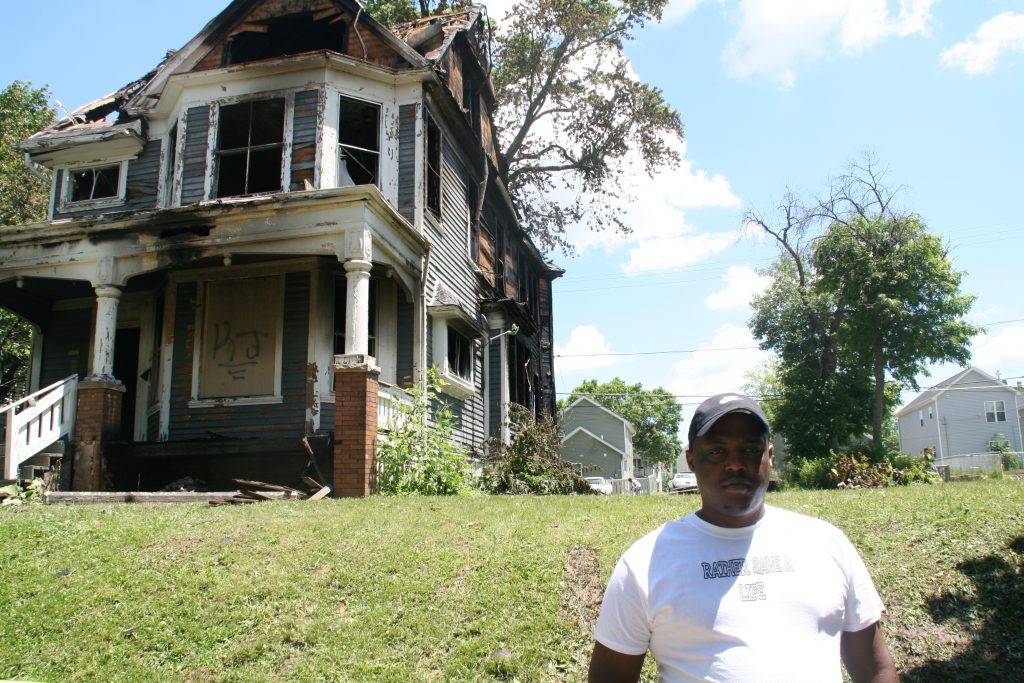 Corey Kirkwood stands in front of the burned home on N. 40th St. Photo by Jeramey Jannene.
