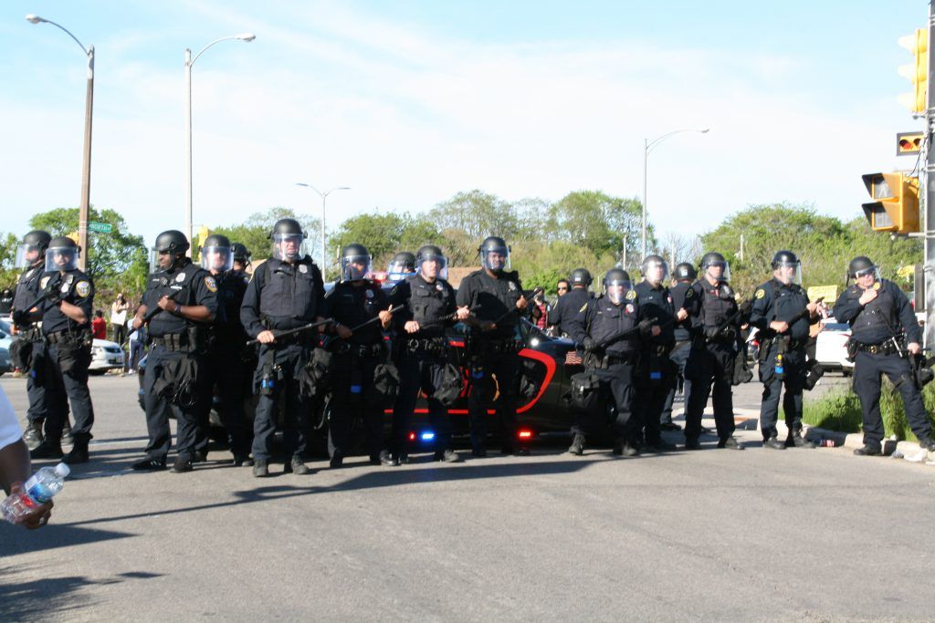 Milwaukee Police Department officers guard a Sheriff's vehicle during the June 2020 protests. Photo by Jeramey Jannene.