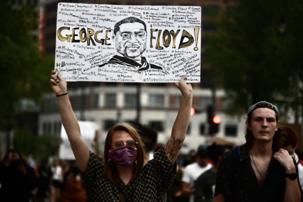 A woman holds a sign honoring George Floyd. Photo by Maddy Day.