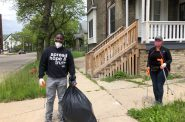 Milwaukee County Executive David Crowley carries a bag of garbage down the street during the June 1st cleanup. Photo by Jeramey Jannene.