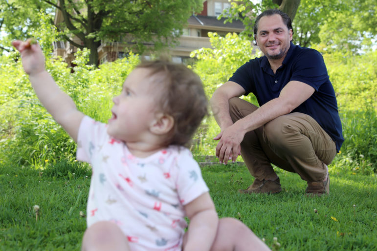 University of Wisconsin-Madison assistant professor Chris Cascio plays with his 14-month-old daughter Juniper in James Madison Park, near the apartment where he lives in Madison, Wis., on May 26, 2020. Cascio was surprised to learn he was on a list of more than 232,000 voters set to be deactivated from the Wisconsin voter rolls after he failed to update his unit number when moving apartments within the same building. While many voters like Cascio have updated their addresses, as of late May, the registrations of about 129,000 voters remained in question. Photo by Coburn Dukehart/Wisconsin Watch.