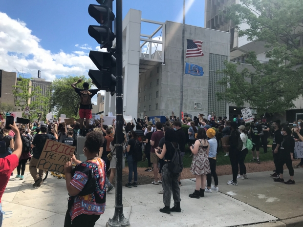 At least 200 protesters marched through downtown Milwaukee before stopping outside the Milwaukee Police Administration building in the 700 block of West State Street on Saturday, May 30, 2020, as officers in riot gear stood by. Madeline Fox/WPR.