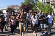 Frank Nitty (red hat) marches between Andre Tripplet (left) and Khalil Coleman (right). Photo by Jeramey Jannene.